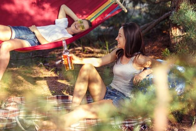 Fête, camping de groupe d'hommes et de femmes à la forêt. ils se détendent et mangent un barbecue contre l'herbe verte. les vacances, l'été, l'aventure, le mode de vie, le concept de pique-nique