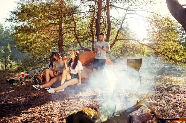 Fête, camping de groupe d'hommes et de femmes en forêt. ils se détendent