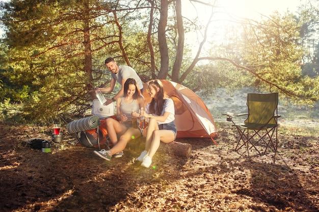 Fête, camping de groupe d'hommes et de femmes en forêt