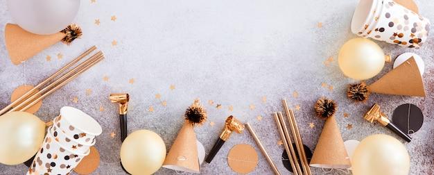 Fête, carnaval, festival et anniversaire fond d'or avec ballon, banderoles colorées et confettis. vue de dessus et mise à plat de la frontière sur un fond de béton blanc. toile de fond panoramique