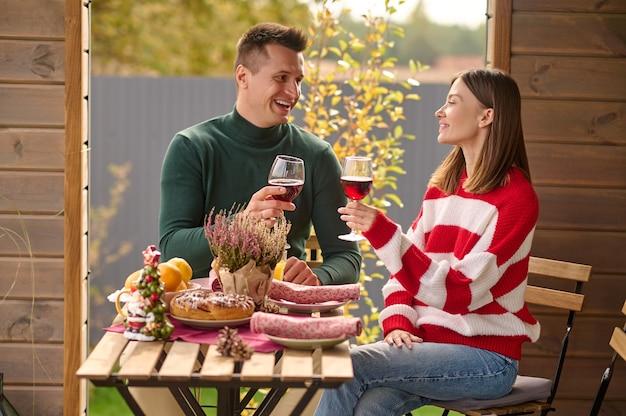 Fête. un couple assis à table avec des verres de vin dans les mains