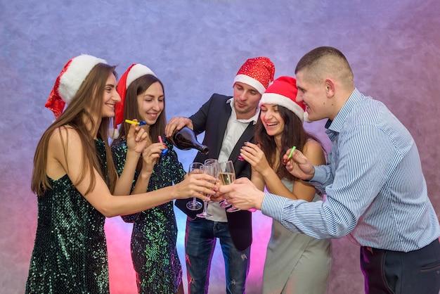 Fête du nouvel an. amis, grillage avec champagne et célébrant le nouvel an