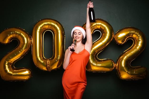 Fête du nouvel an femme brune en bonnet de noel et robe glamour rouge avec des ballons 2022