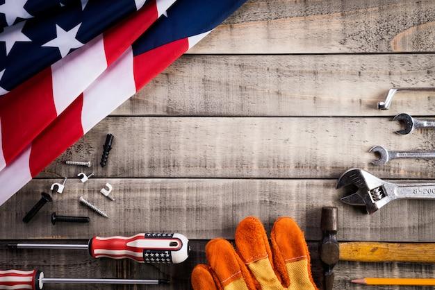 Fête du travail, drapeau usa avec de nombreux outils pratiques sur fond en bois