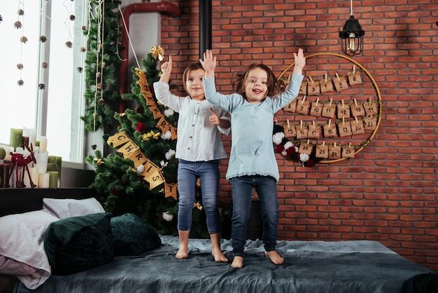 Fête d'enfant dans la belle salle décorée de noël. enfants joyeux s'amusant et sautant sur le lit