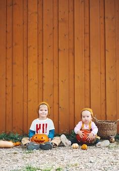 Fête des enfants d'halloween enfants adorables avec des citrouilles sur fond de grange en bois avec espace de copie