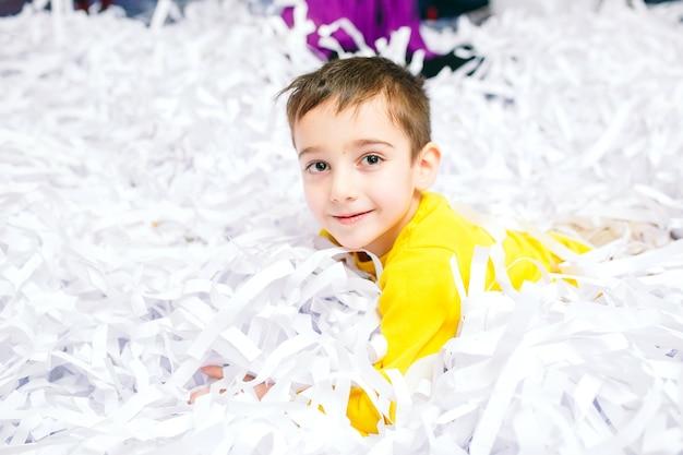 Fête des enfants. petit garçon jouant avec des confettis en papier.