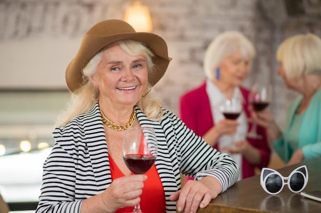 Fête. femme joyeuse dans un chapeau marron tenant un verre de vin