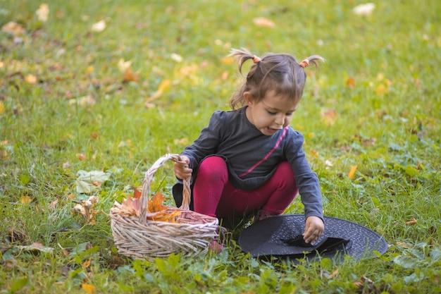 Fête d'halloween. jolie petite fille en robe noire jouant avec un chapeau de sorcière sur une pelouse verte avec des feuilles d'automne.