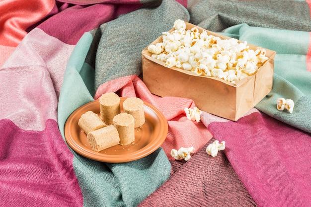 Fête de juin. arachide brésilienne sucrée appelée paçoca sur une assiette et pop-corn sur un tissu coloré..