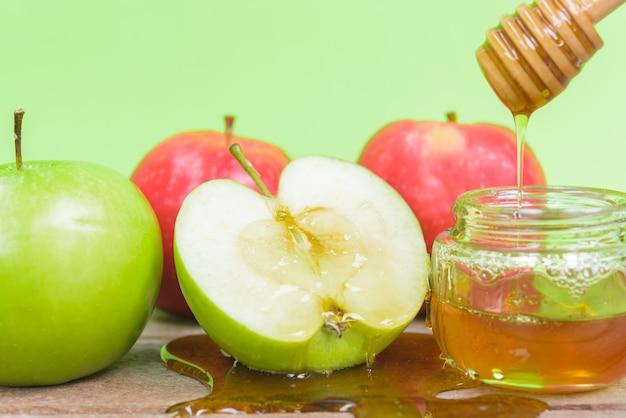 Fête juive apple rosh hashanah la photo a du miel dans un pot et dépose du miel sur des pommes vertes