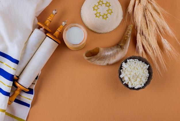 Fête juive de chavouot pour des produits laitiers casher mis sur le rouleau de la torah et le tallis