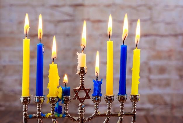 Fête juive menorah avec des bougies pour hanoucca contre les lumières défocalisées