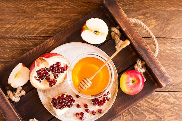 Fête juive roch hachana, pommes miel et grenade sur la table en bois, vue de dessus.