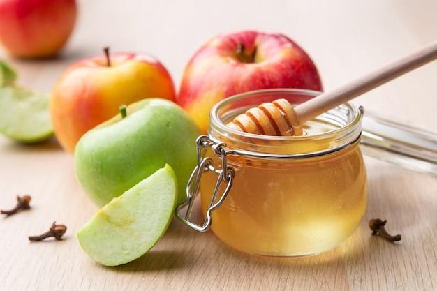 Fête juive de rosh hashana avec du miel et des pommes sur une table en bois.