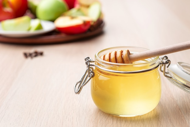 Fête juive de rosh hashana avec du miel et des pommes sur une table en bois,