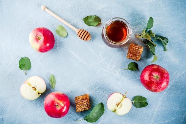 Fête juive rosh hashanah ou concept de fête de pomme, avec pommes rouges, feuilles de pomme et miel en pot