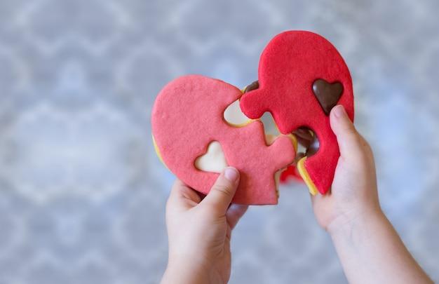 Fête des mères et des familles avec des mains de bébé tenant un détail de biscuit en forme de coeur