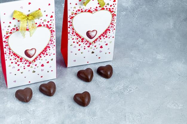 Fête des mères, fête de la femme, saint valentin ou anniversaire sur fond gris. cadeaux, bonbons sous forme de coeurs. copiez l'espace.