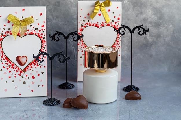 Fête des mères, fête des femmes, saint-valentin ou anniversaire. parfum sur fond gris. cadeaux, bonbons sous forme de coeurs. copiez l'espace.