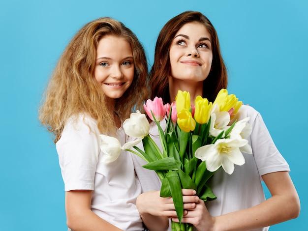 Fête des mères, une jeune femme avec un enfant posant dans le studio avec des fleurs, un cadeau pour la fête des femmes et la fête des mères