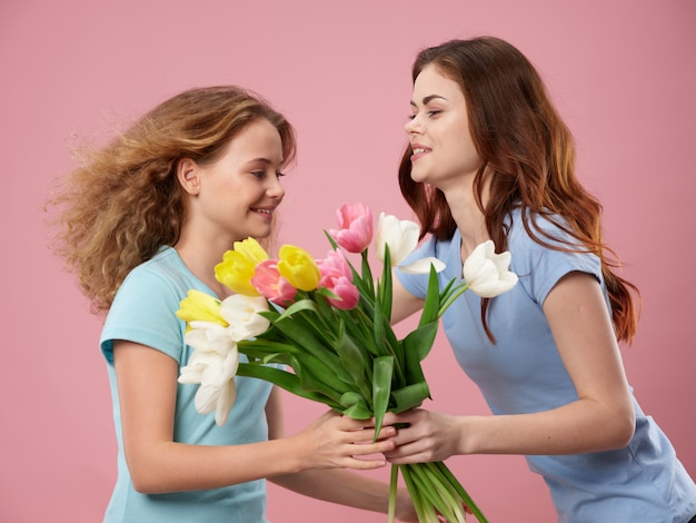 Fête des mères, une jeune femme avec un enfant posant avec des fleurs, un cadeau pour la fête des femmes et la fête des mères
