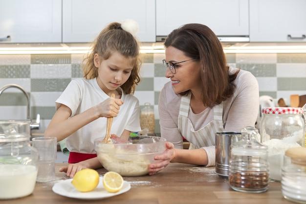 Fête des mères, mère et fille enfant ensemble à la maison cuisine préparer des biscuits, pétrir la pâte dans un bol