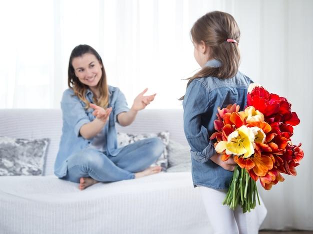 Fête des mères. petite fille avec des fleurs félicite sa mère