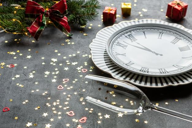Fête de noël et du nouvel an - service en forme d'horloge, bouteilles de champagne, deux verres de champagne et confettis à paillettes dorées,