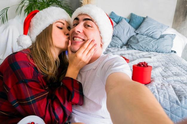 Fête de noël en ligne. femme, baisers, homme, prendre, selfie, porter, chapeaux santa