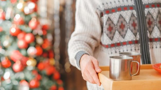 Fête de noël à la maison confortable. photo recadrée de l'homme à l'aide d'un plateau en bois pour servir une boisson chaude dans des tasses en acier