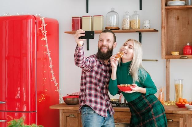 Fête de noël à la maison. couple heureux utilisant le téléphone pour prendre selfie, manger des biscuits en pain d'épice.