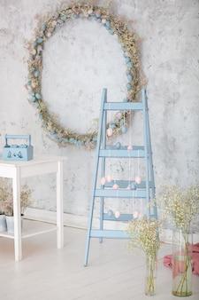 Fête de pâques. échelle bleue de décoration intérieure et mur de guirlande d'oeufs. symbole en bois bricolage décoratif. échelle décorative en bois. décor de chambre de printemps. style rustique. fête de famille. oeufs de pâques colorés
