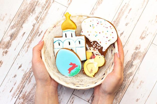 Fête de pâques. oeufs colorés dans un panier. biscuits de pain d'épice de pâques poulet, oeuf, temple, gâteau de pâques dans un panier qui est entre les mains. sur un fond en bois clair.