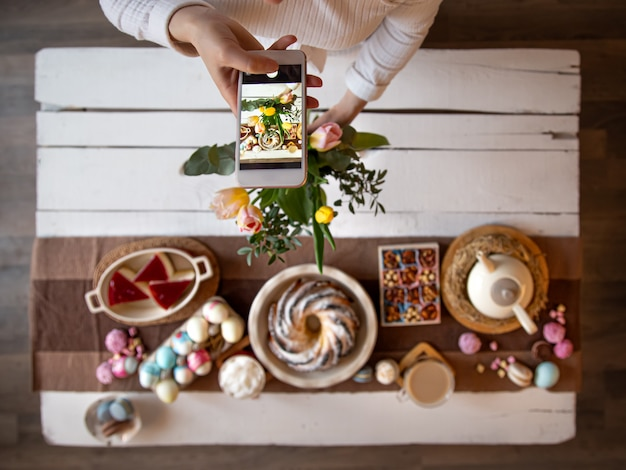 Fête de pâques. photo de votre téléphone, table magnifiquement conservée, pour un déjeuner ou un petit-déjeuner festif de pâques.