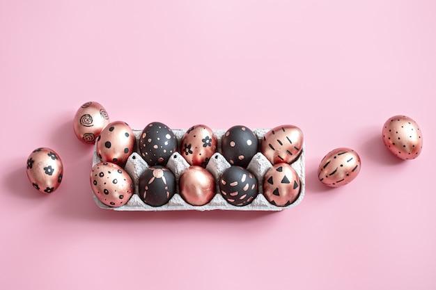 Fête peinte en or et oeufs de pâques noirs sur rose.