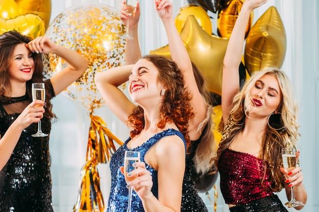 Fête de pendaison de crémaillère de fantaisie. jeune femme heureuse de célébrer sa nouvelle maison avec des amis. jolies filles qui dansent, boivent du champagne.