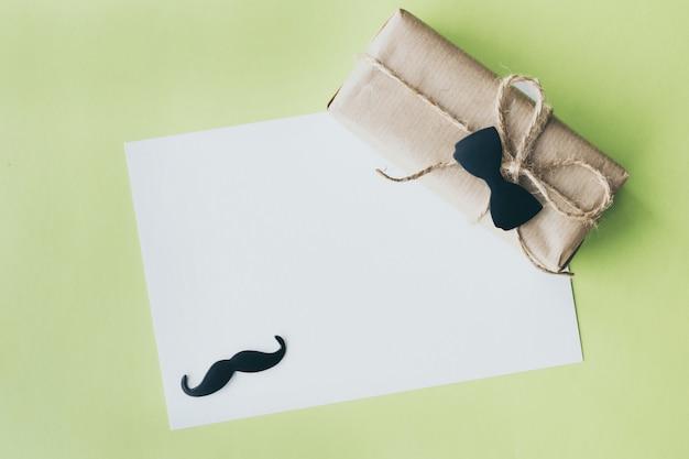 Fête des pères. emballage cadeau enveloppé de papier et de corde avec un nœud papillon décoratif sur fond vert. fond