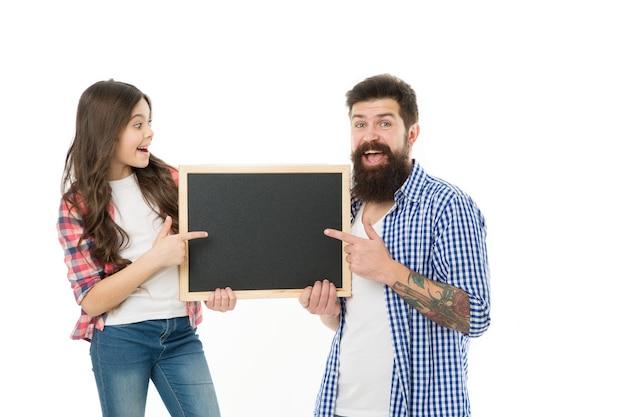 Fête des pères. famille heureuse. père avec fille. petite fille aime son père. journée familiale. petite fille pointant sur le tableau noir de l'école. père et fille tiennent un plateau vide. espace de copie. les pères sourient.