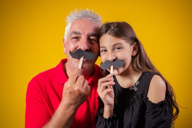 Fête des pères. fille heureuse tenant une petite moustache en papier avec son père sur fond jaune. fille et papa avec moustache en vacances