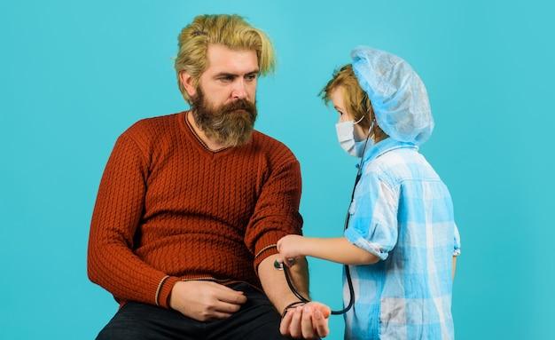Fête des pères. fils joue au docteur avec papa. médecin enfant jouant avec son père. jeu d'enfant.