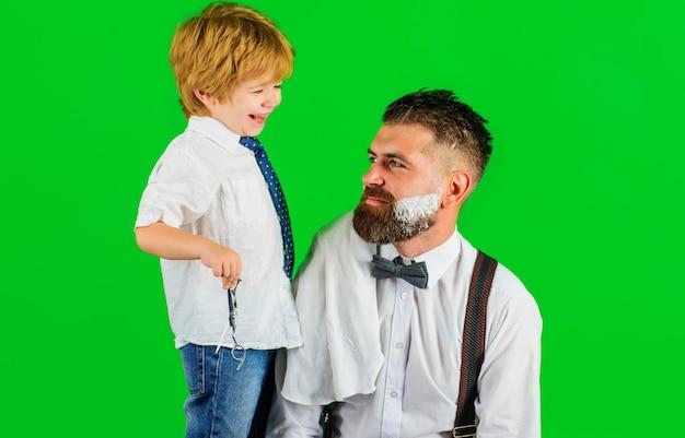 Fête des pères. fils et papa dans le salon de coiffure. rasage de la barbe au salon de coiffure. assistante de papa. salon pour hommes.