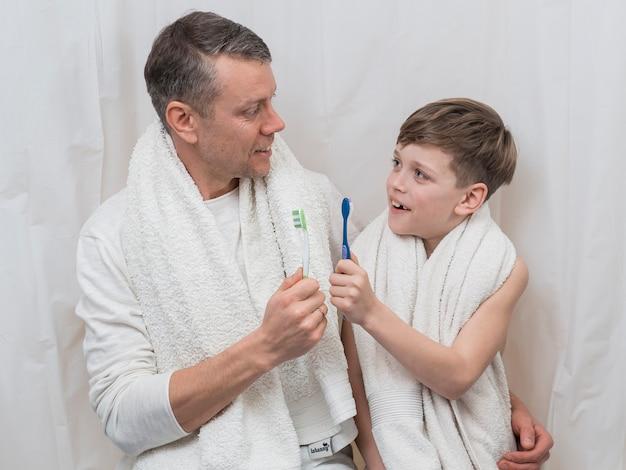 Fête des pères papa et fils tenant des brosses à dents