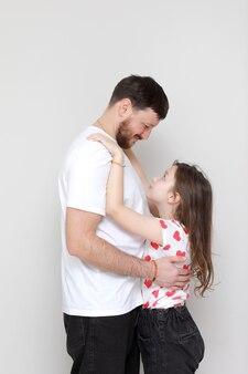 Fête des pères. vue de côté affectueuse petite fille enfant étreint père barbu souriant.