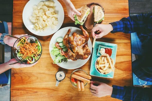 Fête des personnes et manger du poulet grillé sont heureux de profiter de la maison
