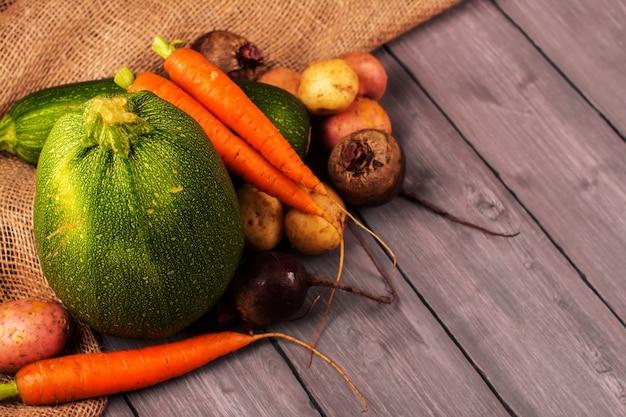 Fête de la récolte. légumes biologiques frais: carotte, pomme de terre, betterave à sucre et courgette sur un fond en bois rustique. image tonique