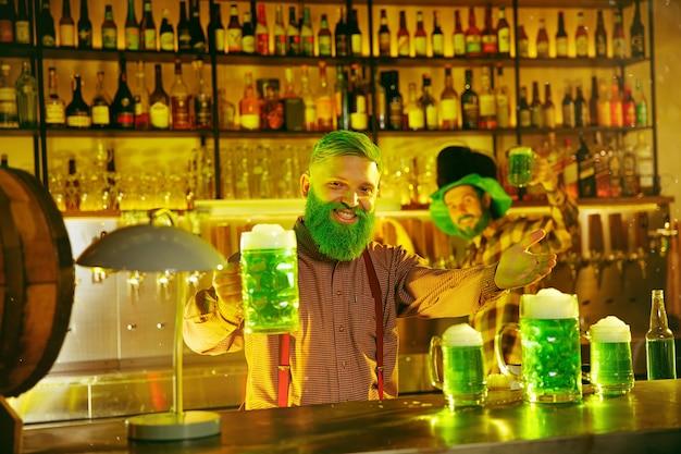 Fête de la saint patrick. des amis heureux célèbrent et boivent de la bière verte. jeunes hommes et femmes portant un chapeau vert. intérieur du pub.