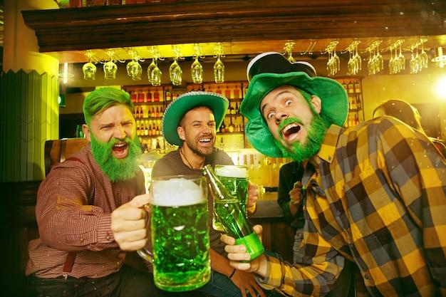 Fête de la saint patrick. des amis heureux célèbrent et boivent de la bière verte. jeunes hommes et femmes portant des chapeaux verts. intérieur du pub.