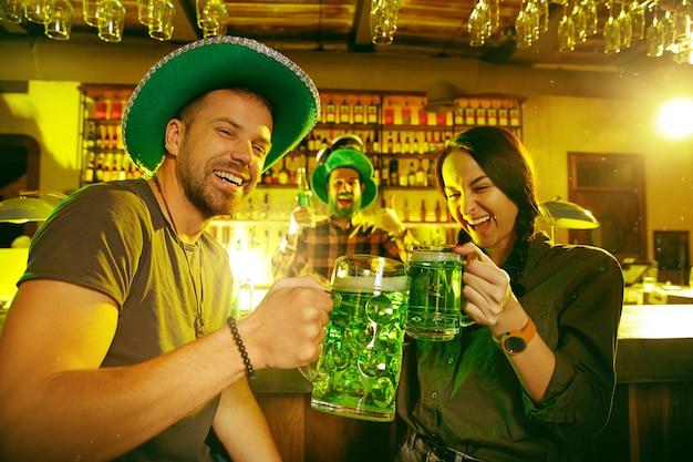 Fête de la saint patrick. des amis heureux célèbrent et boivent de la bière verte.