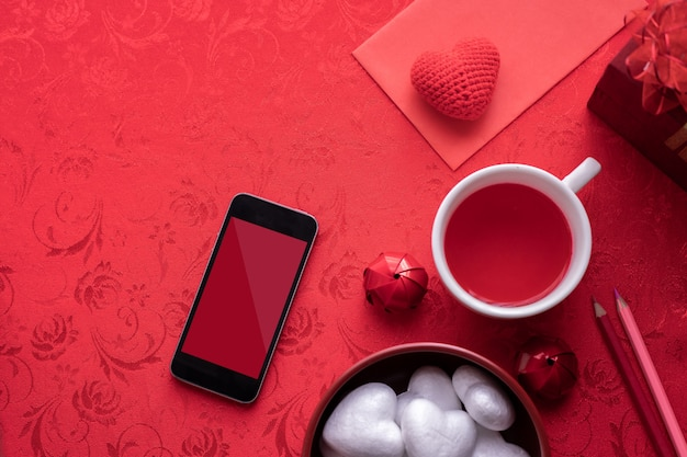 Fête de la saint-valentin avec écran blanc sur smartphone, lettre, boîte-cadeau.